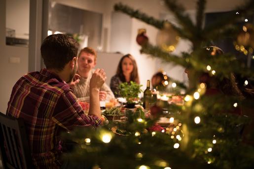 Gjeng med venner rundt et bord og koser seg. Juletre i forgrunnen